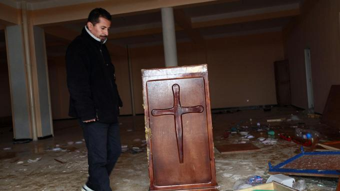An Algerian Protestant looks at damaged and burnt remains at a church in the city of Tizi-Ouzou, 100 km (60 miles) east of the Algerian capital Algiers January 11, 2010. A crowd of men in mostly Muslim Algeria burned Bibles and hymn books in an attack on a Protestant church, prompting the congregation to ask the government for protection from Muslim hardliners. Picture taken January 11, 2010. REUTERS/Louafi Larbi (ALGERIA - Tags: RELIGION CIVIL UNREST) - GM1E61D05VT01